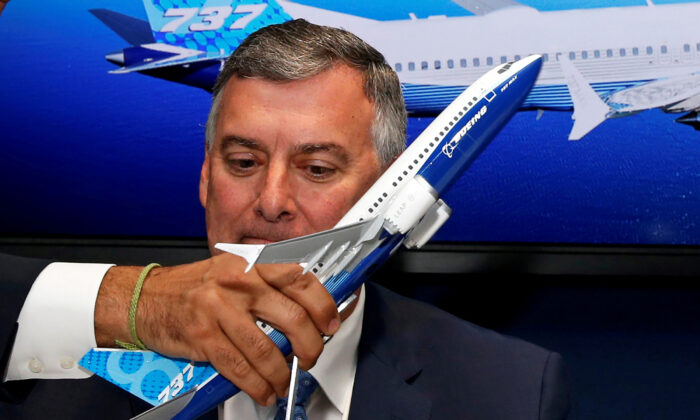 A model of a Boeing 737 MAX is held in front of Kevin McAllister, Boeing Commercial Airplanes CEO, during a commercial announcement at the 53rd International Paris Air Show at Le Bourget Airport near Paris, France, on June 18, 2019. (REUTERS/Pascal Rossignol)