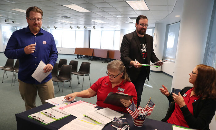 Lance Wissinger (L) and Neil Volz, both with felony records, hand their voter registration forms at the Lee Country Supervisor of Elections office in Fort Myers, Fla., on Jan. 8, 2019.  Joe Raedle/Getty Images