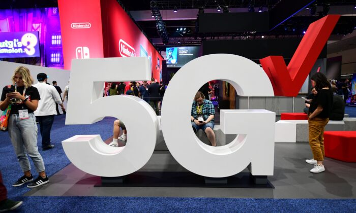 Cellphone users stand beside a Verizon 5G display at the 2019 Electronic Entertainment Expo, also known as E3, in Los Angeles, California, U.S. on June 12, 2019. (Frederic J. Brown/AFP/Getty Images)