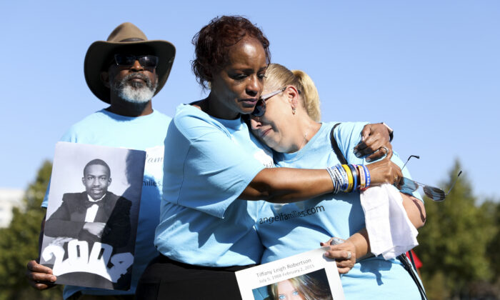 Angel parents comfort each other while holding pictures of their loved ones, who were killed by illegal aliens, at an event outside the Capitol building in Washington on Sept. 25, 2019. (Samira Bouaou/The Epoch Times)