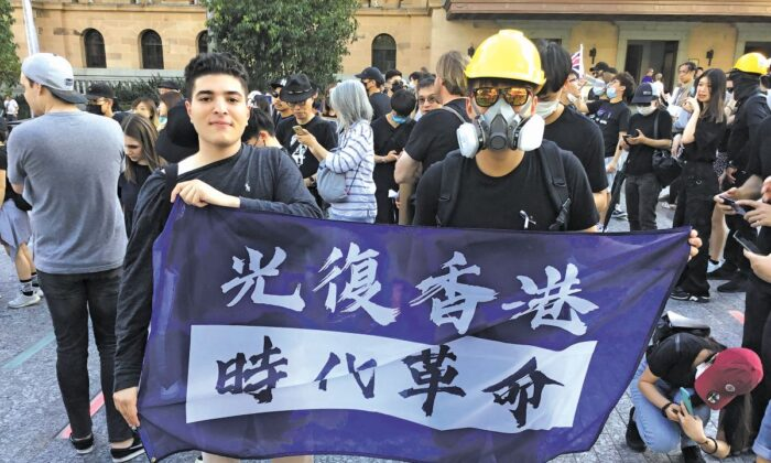 "Drew Pavlou (left), 20, at a protest holding a banner saying ""Liberate Hong Kong, revolution of our times."" (Courtesy of Drew Pavlou)"