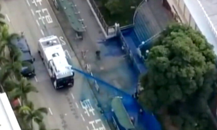 Camera equipped on The Epoch Times' drone shoots the moment police fired a water cannon at the Kowloon Masjid and Islamic Center with blue dye when a few people were standing in front of it on Oct. 20, 2019. (The Epoch Times)