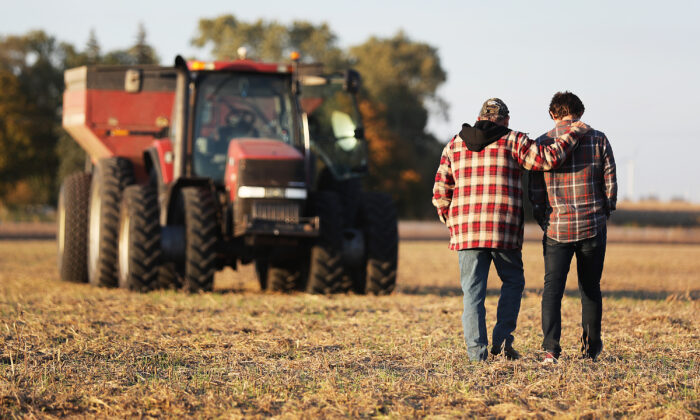 Roy Bardole walks with his grandson Gabe Bardole during the soybean harvest at the Bardole & Son's Ltd farm, in Rippey, Iowa, on Oct. 14, 2019. (Joe Raedle/Getty Images)