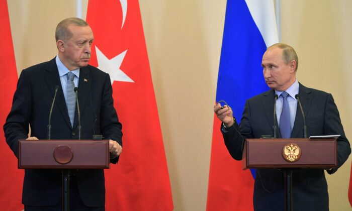 Russian President Vladimir Putin, right, and Turkish President Recep Tayyip Erdogan look at each other during a joint news conference after their talks in the Bocharov Ruchei residence in the Black Sea resort of Sochi, Russia on Oct. 22, 2019. (Alexei Druzhinin/Sputnik Kremlin Pool Photo via AP)