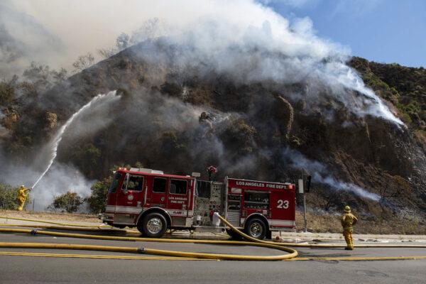Firefighters begin hosing down the flames
