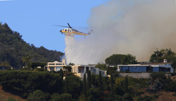 A helicopter makes a water drop as flames threaten homes