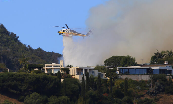 A helicopter makes a water drop as flames threaten homes on a ridgeline as a wildfire threatens homes in the Pacific Palisades area of Los Angeles on Oct. 21, 2019. (Reed Saxon/AP Photo)