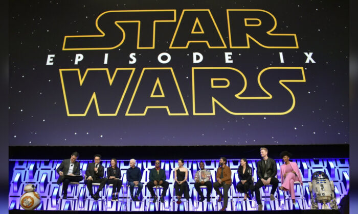 """Stephen Colbert, from left, J.J. Abrams, Kathleen Kennedy, Anthony Daniels, Billy Dee Williams, Daisy Ridley, John Boyega, Oscar Isaac, Kelly Marie Tran, Joonas Suotamo and Naomi Ackie participate in the """"Star Wars: The Rise of Skywalker"""" panel on day 1 of the Star Wars Celebration at Wintrust Arena in Chicago on April 12, 2019. (Rob Grabowski/Invision/AP)"""