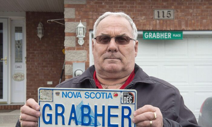 """Lorne Grabher displays his personalized licence plate in Dartmouth, N.S., on March 24, 2017. Deemed offensive to women, the eponymous plate was revoked in 2016 following an anonymous complaint. An Indigenous man in Manitoba has had his NDN CAR personalized licence plate returned, but an avid """"Star Trek"""" fan lost his court fight to use his Borg-themed plate. (THE CANADIAN PRESS/Andrew Vaughan)"""