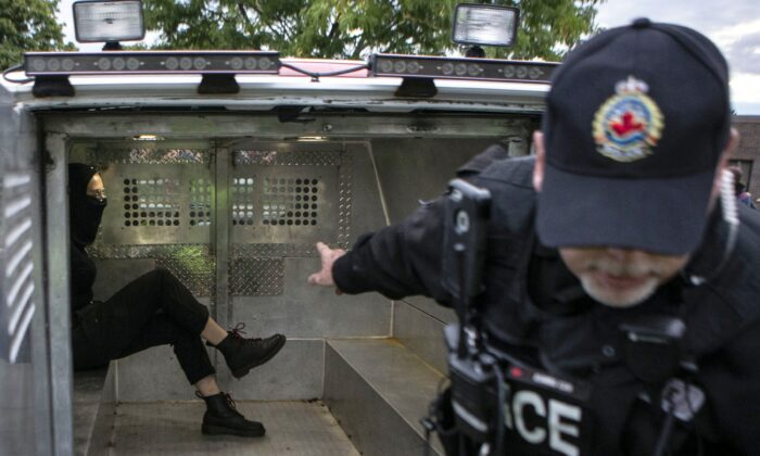 A black-clad masked man sits in a police van after being arrested at a demonstration prior to a  People's Party of Canada event in Hamilton, Ont., on Sept. 29, 2019. Three people have been charged in connection with a protest outside the event featuring PPC Leader Maxime Bernier, including a man whose family temporarily shut down their business amid backlash over his participation. (THE CANADIAN PRESS/Chris Young)
