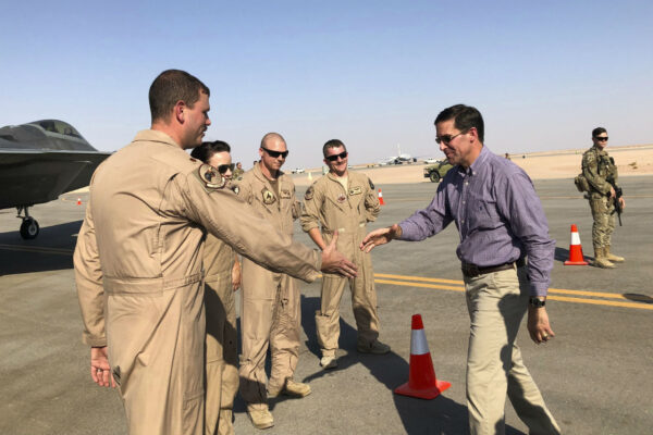 Defense Secretary Mark Esper talks with U.S. troops in front of an F-22 fighter jet deployed to Prince Sultan Air Base in Saudi Arabia, Tuesday, Oct. 22, 2019. (Lolita Baldor/AP Photo)