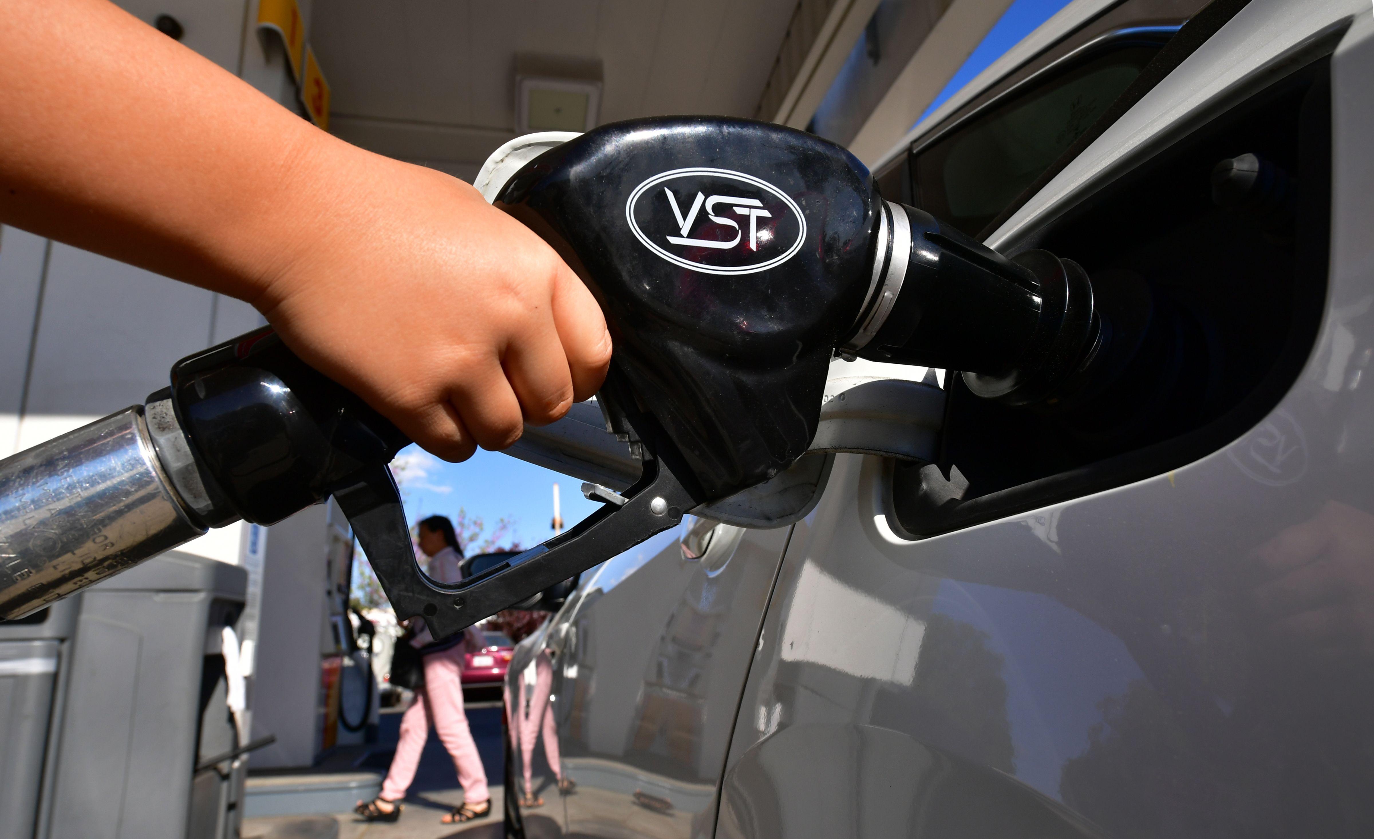 A child pumps gas