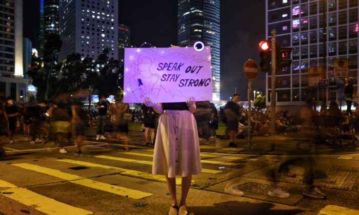 A protester holds a sign at a #MeToo rally to protest alleged sexual assaults by police against pro-democracy female protesters, in Hong Kong on Aug. 28, 2019. (Lillian  Suwanrumpha/AFP/Getty Images)