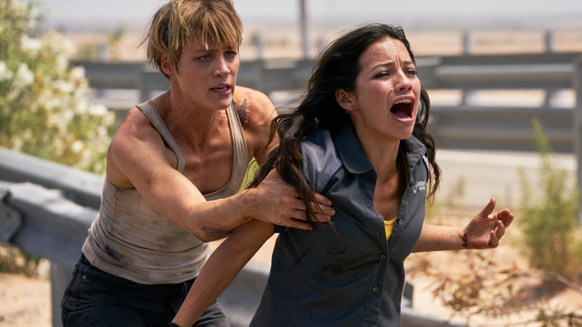 blonde woman in white tank top restrains woman with dark hair