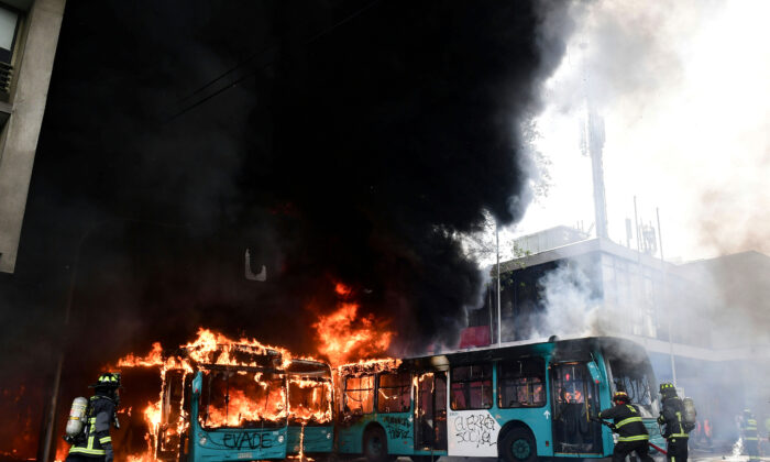 Chilean firefighters extinguish burning buses during clashes between protesters and the riot police in Santiago, on Oct. 19, 2019. (MARTIN BERNETTI/AFP via Getty Images)