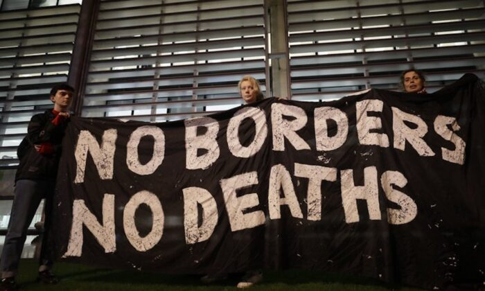 Demonstrators hold a banner during a vigil for the 39 lorry victims, outside the Home Office in London on Oct. 24, 2019. Authorities found 39 people dead in a truck in an industrial park in England on Oct. 23 and arrested the driver on suspicion of murder in one of Britain's worst human-smuggling tragedies. (Kirsty Wigglesworth/AP)