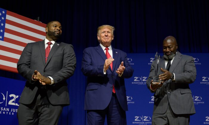 President Donald Trump (C) is awarded the Bipartisan Justice Award by Matthew Charles (R), who was released from federal prison through the First Step Act, prior to delivering remarks at the 2019 Second Step Presidential Justice Forum in Columbia, South Carolina on Oct. 25, 2019. (Jim Watson/AFP via Getty Images)