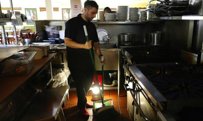 Salvador Espinosa sweeps in the kitchen of a Mary's Pizza Shack restaurant during a Pacific Gas and Electric Co. power shutdown in Santa Rosa, Calif., on Oct. 10, 2019. (Christopher Chung/The Press Democrat via AP)
