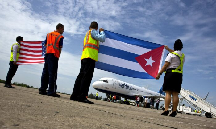 Airport workers receive JetBlue flight 387, the first commercial flight between the U.S. and Cuba in more than a half century, holding a United States, and a Cuban national flag, on the airport tarmac in Santa Clara, Cuba on Aug. 31, 2016. (Ramon Espinosa/File Photo via AP)