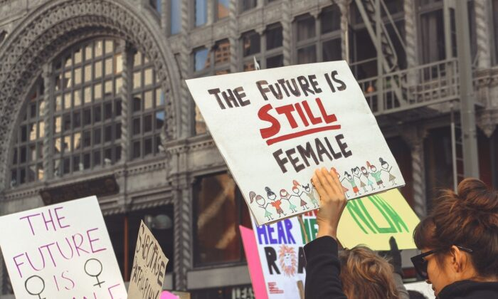 "Participants in the Women's March 2018 hold signs saying ""The Future is Female."" Men and traditional masculinity are under attack, concludes Nicole Russell, after reading GQ's latest issue on masculinity. (Miawicks9/Pixabay)"
