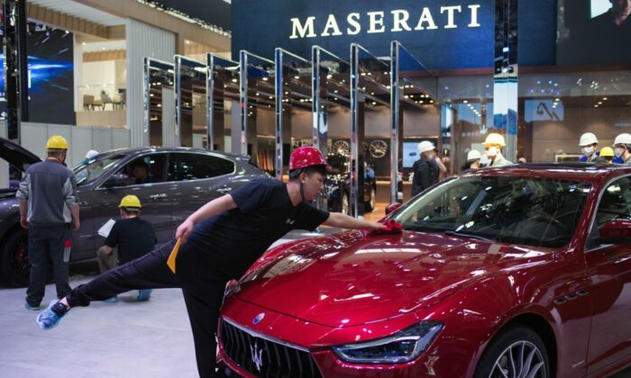 A worker stretches out to dust off a Maserati car on the eve of the Beijing Auto Show in Beijing on April 24, 2018. (Nicolas Asfouri/AFP/Getty Images)