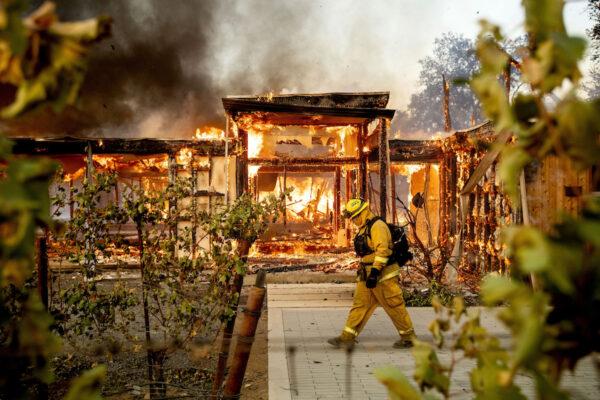 Firefighter Joe Zurilgen passes a burning home