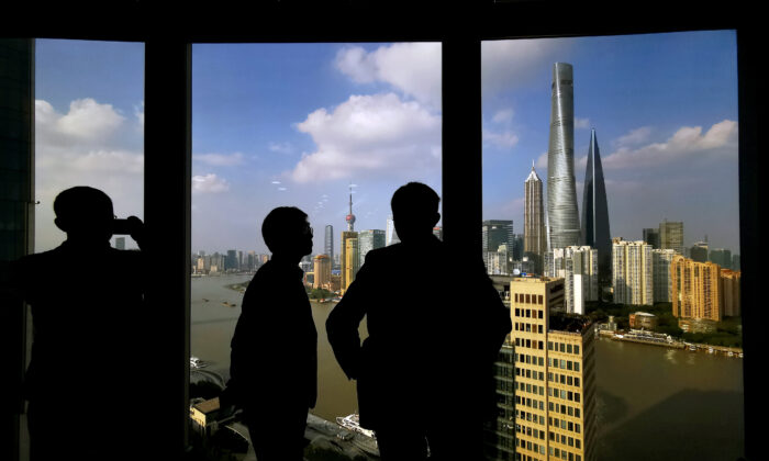 People stand near a window overlooking the financial district in Shanghai, China on Oct. 23, 2019. (Reuters)