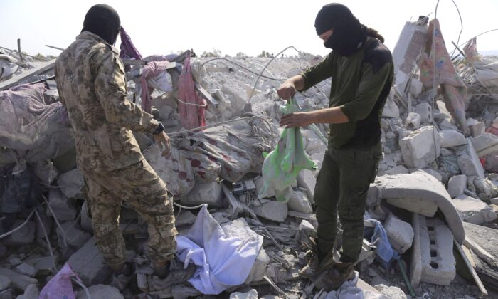 """Two men stand in rubble near the village of Barisha, in Idlib province, Syria, on Oct. 27, 2019, after an operation by the U.S. military which targeted Abu Bakr al-Baghdadi, the shadowy leader of the ISIS terrorist group. The federal government says Canada's national-threat level remains at """"medium"""" despite the leader of the Islamic State group having been killed over the weekend. (THE CANADIAN PRESS/AP, Ghaith Alsayed)"""