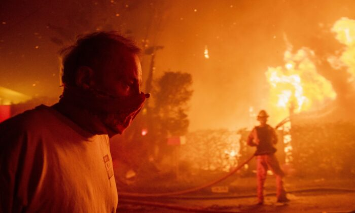A man walks past a burning home during the Getty fire, Monday, Oct. 28, 2019, in Los Angeles, Calif. (AP Photo/ Christian Monterrosa)