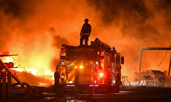 A firefighter stops to look at a wall of fire while battling a grass fire on East Cypress Road in Knightsen, Calif., on Oct. 27, 2019. (Jose Carlos Fajardo/Bay Area News Group/San Jose Mercury News via AP)