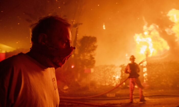 A man walks past a burning home during the Getty fire on Oct. 28, 2019, in Los Angeles, Calif. (Christian Monterrosa/AP Photo)