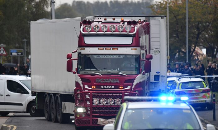 Police officers drive away a lorry (C) in which 39 dead bodies were discovered sparking a murder investigation at Waterglade Industrial Park in Grays, east of London, on Oct. 23, 2019. (Ben Stansall/AFP/Getty Images)