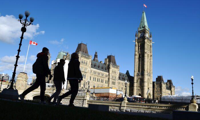 People walk near Parliament Hill in Ottawa on Oct. 23, 2019. (THE CANADIAN PRESS/Sean Kilpatrick)