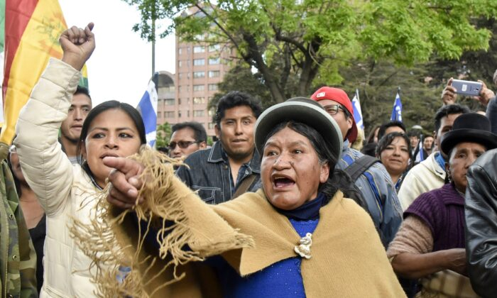 Supporters of Bolivia's president and candidate Evo Morales demonstrate against the main opposition candidate, former president (2003-2005) Carlos Mesa, as supporters of both groups gather outside the hotel where the Supreme Electoral Tribunal has its headquarters to count the election votes, in La Paz, on October 21, 2019. (AIZAR RALDES/AFP via Getty Images)