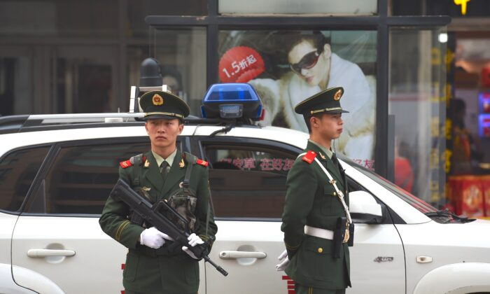 """Chinese paramilitary police officers watch over pedestrians in the Wangfujing shopping district in Beijing on Oct. 24, 2014. China's Communist rulers declared that the country would embrace the """"rule of law with Chinese characteristics,"""" official media reported after a key party meeting touted as heralding legal reform. (Greg Baker/AFP/Getty Images)"""