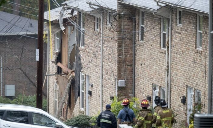 Fire officials look at the scene where an airplane crashed into an apartment complex in Atlanta, Ga., on Oct. 30, 2019. (AP Photo/David Goldman)