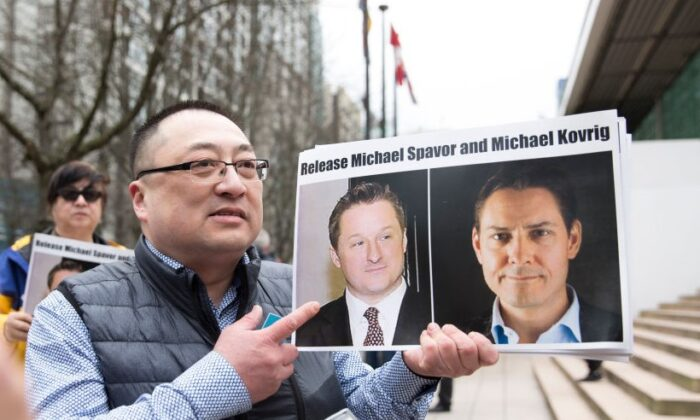 Louis Huang of Freedom and Democracy for China holds photos of Canadians Michael Spavor and Michael Kovrig, who have been arrested by China, outside the British Columbia Supreme Court in Vancouver on March 6, 2019. (Jason Redmond/AFP/Getty Images)
