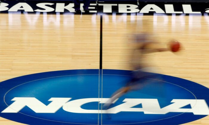 A player runs across the NCAA logo during practice at the NCAA tournament college basketball in Pittsburgh on March 14, 2012. (Keith Srakocic, File, AP Photo)