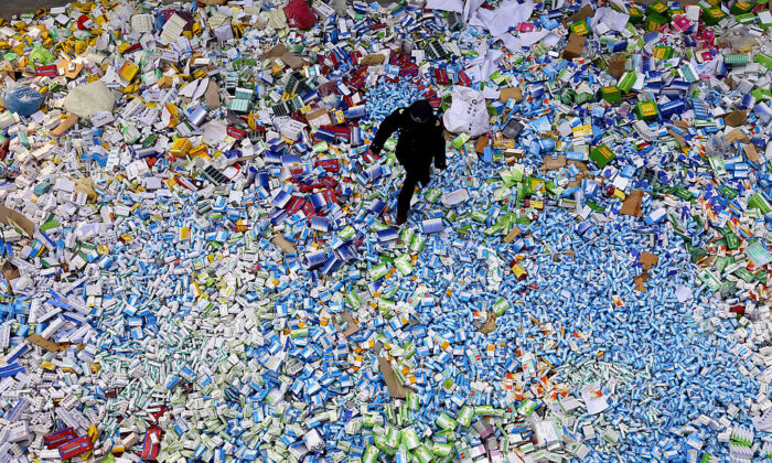 A Chinese policeman walks across a pile of fake medicines seized in Beijing in recent months on March 14, 2013. (STR/AFP via Getty Images)