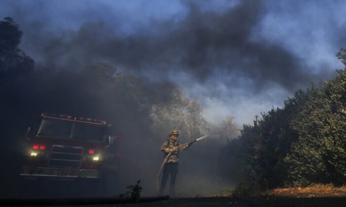 Firefighter Brett Reed battles a wildfire near a ranch in Simi Valley, Calif., on Oct. 30, 2019. (Ringo H.W. Chiu/AP)