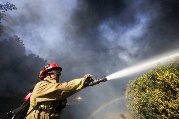 A firefighter battles a wildfire near a ranch in Simi Valley, Calif.