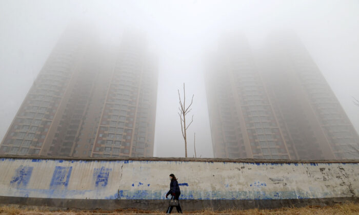 A woman wearing a mask walks past buildings on a polluted day in Handan, Hebei Province, China on Jan. 12, 2019. (Reuters)