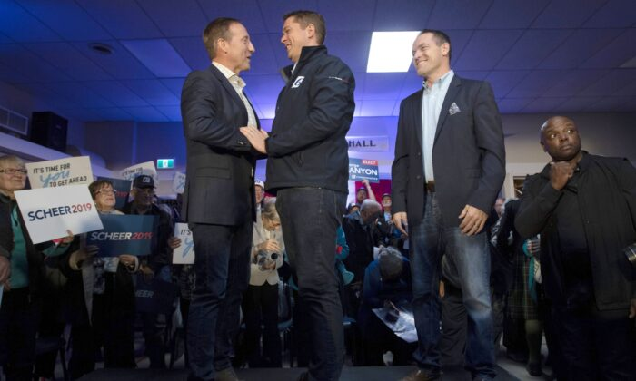 Conservative leader Andrew Scheer shakes hands with Peter MacKay as local Conservative candidate George Canyon looks on during a campaign stop in Little Harbour, N.S., on Oct. 17, 2019. (THE CANADIAN PRESS/Adrian Wyld)