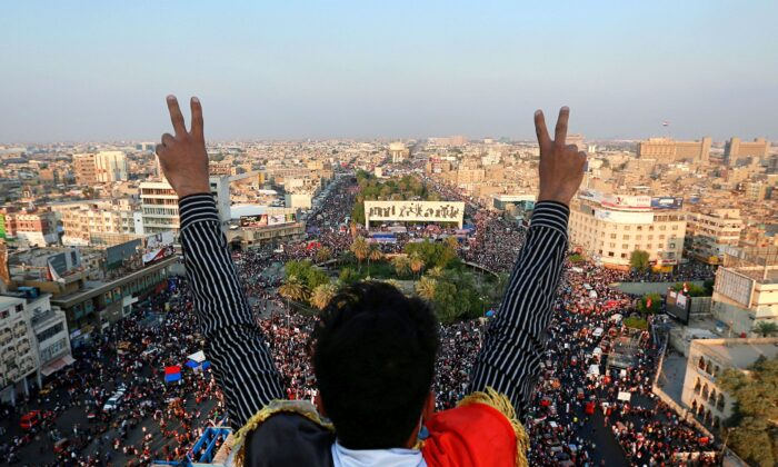 A protester gives the victory sign as thousands of anti-government protesters gather in Tahrir Square during ongoing demonstrations in Baghdad, Iraq, on Oct. 31, 2019. (AP Photo/Hadi Mizban)