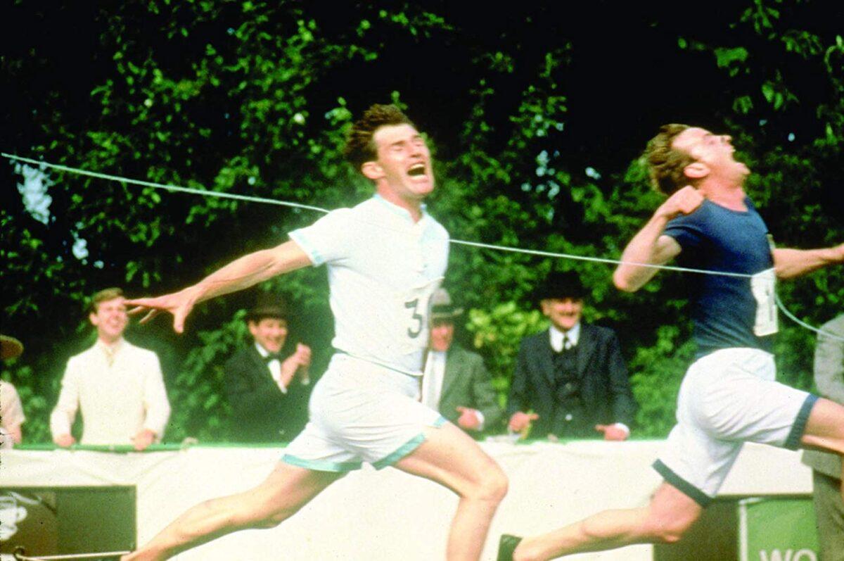 two men breaking finish line tape