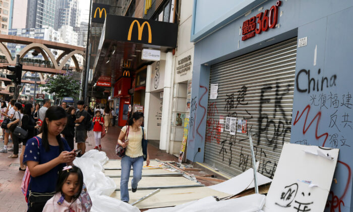 People walk past a vandalized store in Causeway Bay district, in Hong Kong, China on Oct. 8, 2019. (Susana Vera/Reuters)