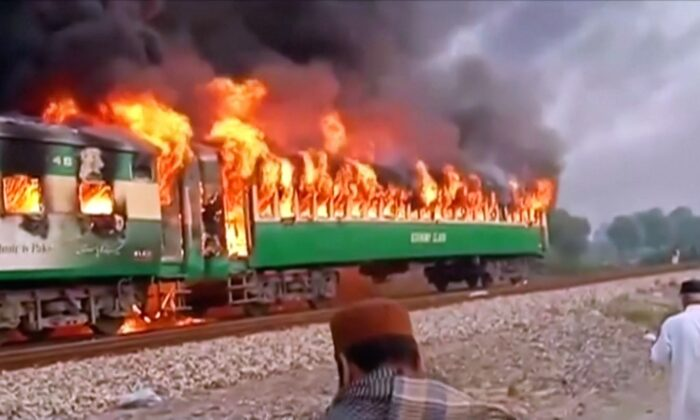 A fire burns a train carriage after a gas canister passengers were using to cook breakfast exploded, near the town of Rahim Yar Khan in the south of Punjab province, Pakistan on Oct. 31, 2019, in this still image take from video. (Asghar Bhawalpuri/via Reuters TV)