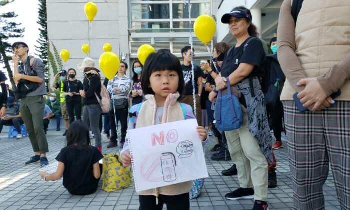 A girl holds a sketch showing no to tear gas at a rally at Edinburgh Place in Hong Kong, on Dec. 1, 2019. (Bill Cox/The Epoch Times)