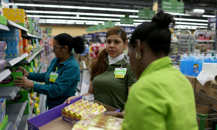 Walmart employee Yanetsi Grave (C) and her fellow employees stock the shelves at a Walmart store on Feb. 19, 2015 in Miami, Fla. (Joe Raedle/Getty Images)