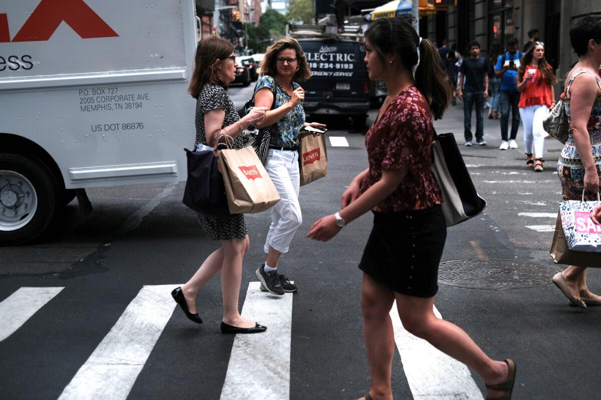 People walk along a shopping street